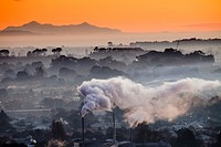 Winter dawn over industrial chimneys, Christchurch, Seaward Kaikoura range behind, New Zealand
