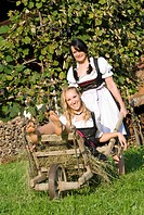 women in dirndl with wheelbarrow