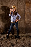 Portrait of young cowgirl standing in horse stable tipping cowboy hat