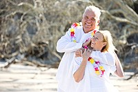 Affectionate mature couple in leis on the beach