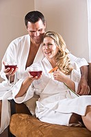 Mid adult couple in bathrobes sitting together on sofa drinking wine