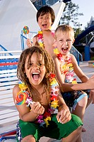 Boys with lollipops and flower leis at water park in summer