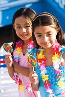 Two young girls holding lollipops