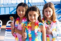 Girls with lollipops and flower leis on pool deck in summer