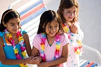 Three happy young girls at water park wearing flower leis