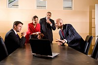 Multi_ethnic business managers looking at laptop in boardroom