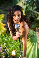Young Hispanic woman singing on tropical island