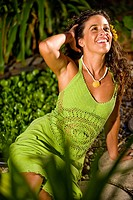 Young Hispanic woman in green dress on tropical island