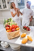 Mid adult couple laughing in kitchen with fresh fruits and vegetables
