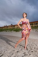 Young woman in colorful sundress standing on beach in front of resort