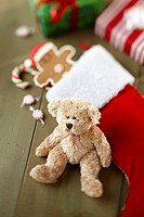 Teddy bear beside Christmas stocking with candy and cookies