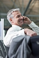Businessman talking on cell phone in airport terminal