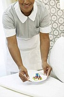 Housekeeper putting a plate of candies on the bed