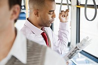 Businessman reading newspaper while standing on public bus