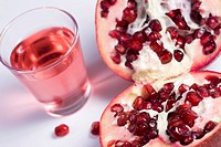 Pomegranate fruit cut in half and pomegranate juice