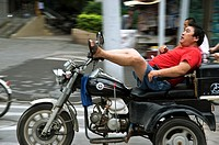 Man driving a motorcycle with his feet on the streets of Shanghai