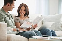 Hispanic couple reviewing monthly bills