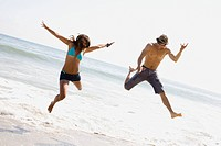Couple jumping on beach together