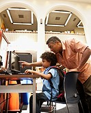 Man helping mixed race boy use computer