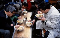 Eating bowls of noodles on the street, Tokyo, Japan