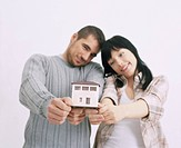 Couple holding little house
