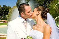 Closeup of a newlywed couple in white dress kissing in a park