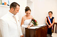 Bride and groom signing legal documents in the registry office