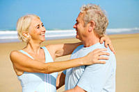Retired couple hugging on the beach on a sunny day