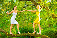 Two girls dancing on the branch of tree in a park on summers day