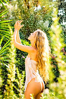 Young woman enjoying the refreshing waterdrops on her body on a sunny day