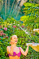 Girl dressed in a bikini playing around with the water from a fountain in a garden