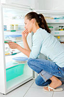 Young woman looking in the fridge for food