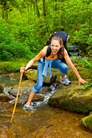 Young woman hiking through the woods and trying to cross a stream and accidentally falling into the water