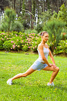 Young woman excercising in the garden get in shape on a beautiful day
