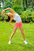 Young woman excercising in the garden and stretching