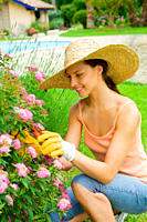 Young woman wearing a straw hat taking care of the garden work on a beautiful day