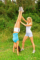 Two women dressed in sporty clothes working out outdoors and helping each other to complete a handstand