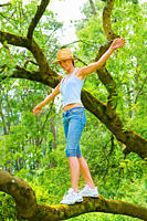 Young woman balancing on a tree on a beautiful day