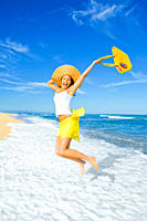 Young woman with a straw hat and bag jumping over the waves at the beach