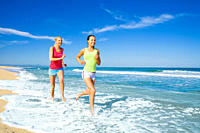 Two women exercising and jogging along the beautiful sandy beach