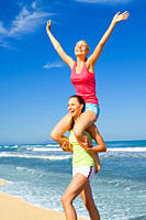 Two women working out on a beach and giving each other a piggyback ride