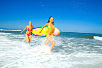 Two young women jogging through the water on the beach holding a surfboard