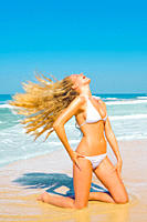 Young woman enjoying the day at the beach and swirling her hair arround