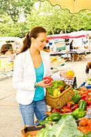 Young woman buying healthy food on the market