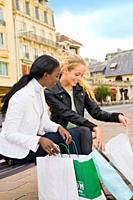 Caucasian and african woman sitting on a bench and showing each other what they bought