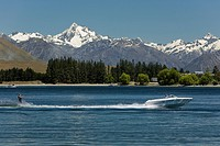 Waterskier behind a motorboat on Lake Camp with views of the mountains of Cloudy Peak Range, South Island, New Zealand