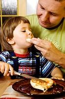 Man feeding his son.