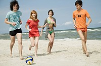 Four friends playing volleyball on the beach.