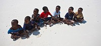 Children sitting in a row on the beach, Zanzibar, Tanzania, Africa