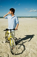 Boy with bike on the beach